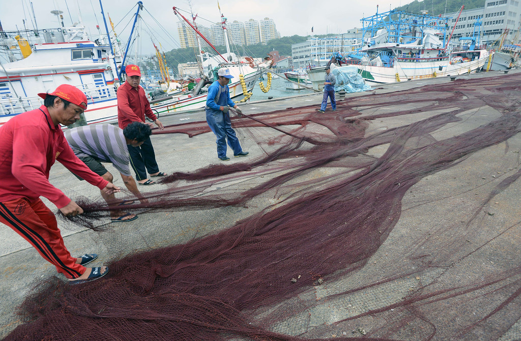 . Foreign fish workers adjust a net at the Patoutze fish harbor, in Keelung, northern Taiwan on October 5, 2013.  Taiwan on October 5 issued a warning over Typhoon Fitow as it approached the island\'s north with threats of torrential rains and powerful winds over the weekend.   SAM YEH/AFP/Getty Images