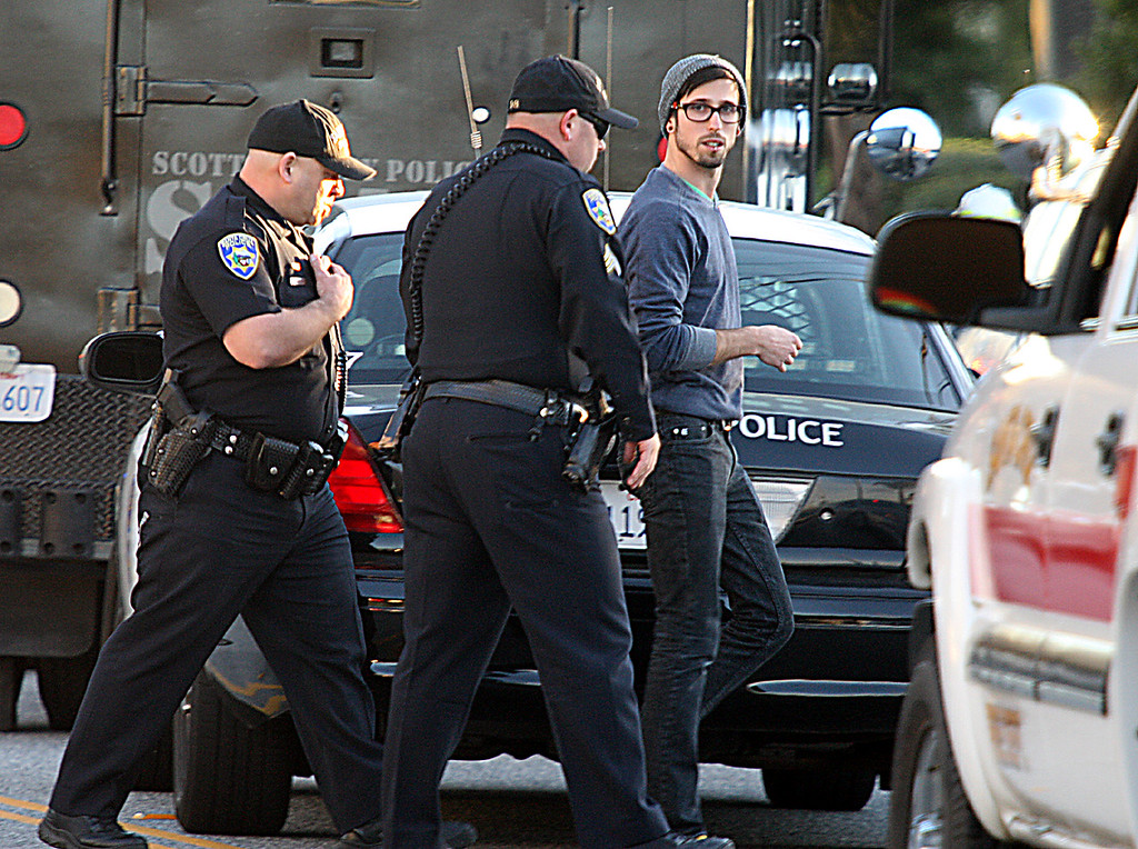 . Santa Cruz Police offers bring a man to the shooting scene commnand center where he looked through police photos and provided information to an interviewing officer.  (Dan Coyro/Sentinel)