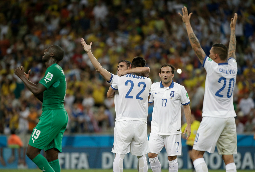 . Ivory Coast\'s Yaya Toure reacts as Greek players celebrate after their 2-1 victory over Ivory Coast during the group C World Cup soccer match between Greece and Ivory Coast at the Arena Castelao in Fortaleza, Brazil, Tuesday, June 24, 2014. (AP Photo/Bernat Armangue)