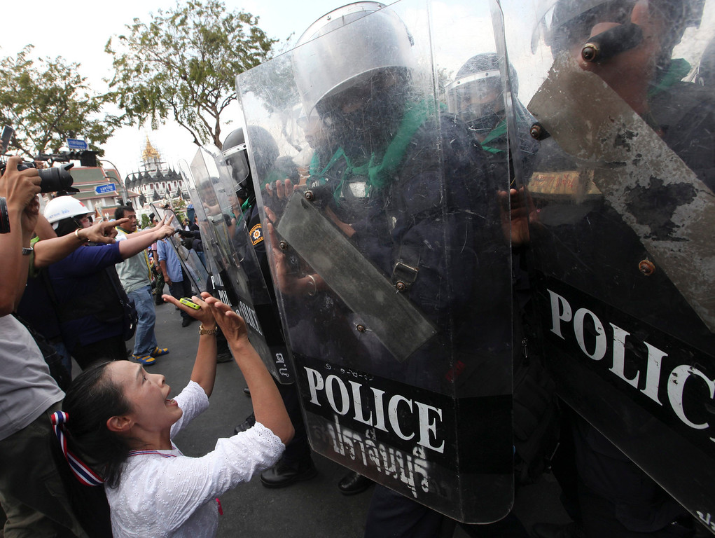. Thai riot police officers face with anti-government protesters during clashes at a protest site near Democracy Monument in Bangkok, Thailand, 18 February 2014.  EPA/PETER CHAN