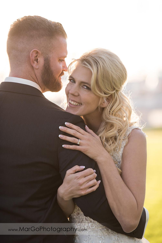 bride hugging groom's arm during wedding reception at San Diego Mission Bay Park