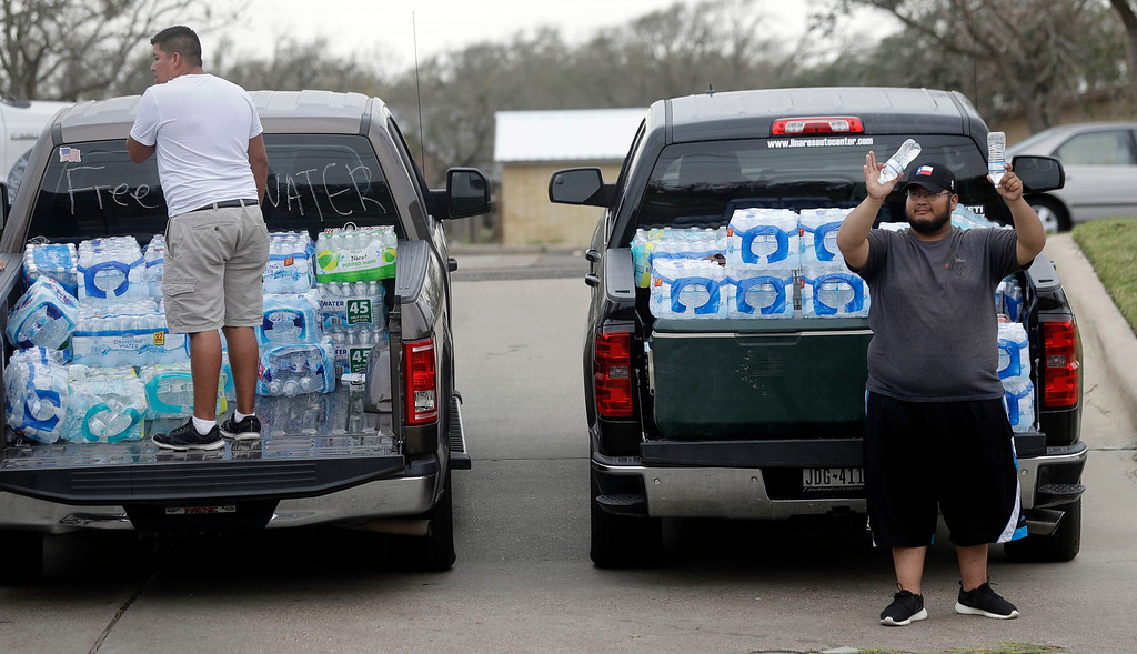 . Miguel Juarez, right, offers free water to passing vehicles Sunday, Aug. 27, 2017, in Rockport, Texas. Juarez and others from the Texas Rio Grande Valley created a make-shift aid station for in need following Hurricane Harvey. (AP Photo/Eric Gay)