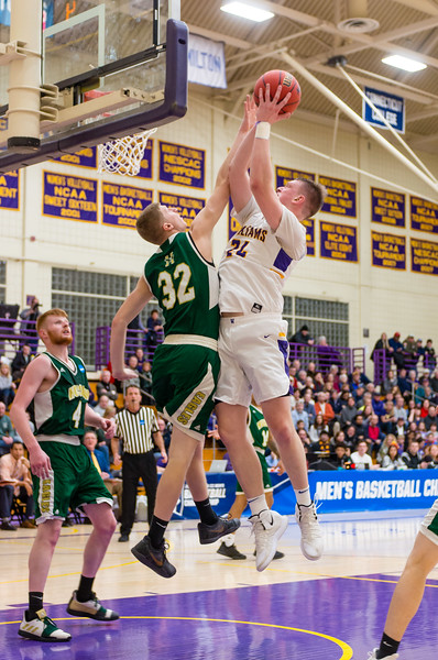 Matt Karpowicz (24) goes up for a shot over the Husson's Justin Martin (32)