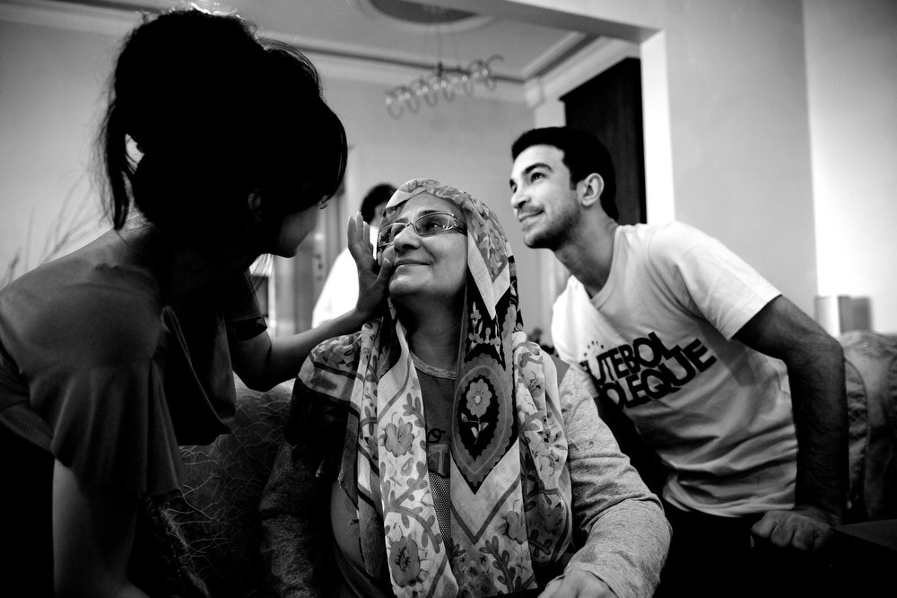 . Breast cancer patient Soheila Mehri, and her children Sara (L) and Hossein (R) congratulate each other at the beginning of Noruz festival at their house in Tehran on March 20, 2013, on the first day of new Persian year.  AFP PHOTO/BEHROUZ MEHRI