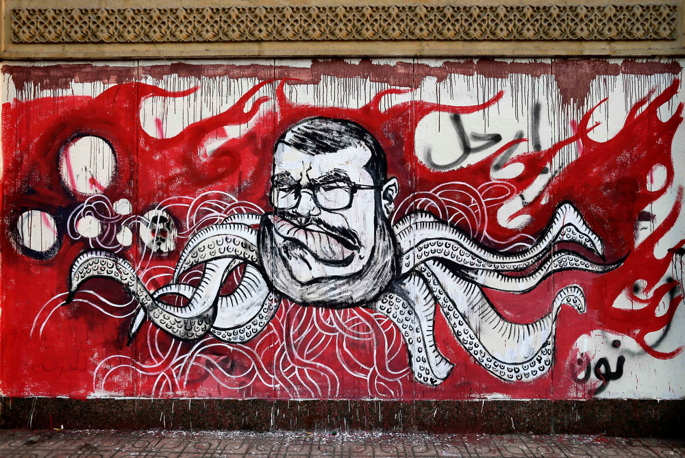 Description of . Graffiti depicting Egyptian President Mohamed Morsi covers an outer wall of the presidential palace in Cairo, Egypt, Saturday, Dec. 8, 2012. Egypt\'s military warned Saturday of \'disastrous consequences\' if the crisis that sent tens of thousands of protesters back into the streets is not resolved, signaling the army\'s return to an increasingly polarized and violent political scene. (AP Photo/Hassan Ammar)