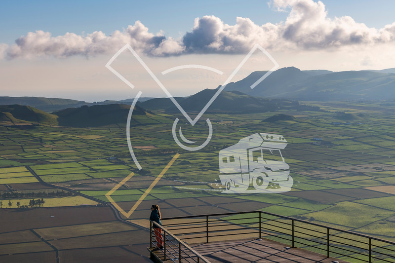 A young woman enjoying and observing the view of fields from the viewing platform of Miradouro da Serra do Cume on Terceira island at a beautiful sunset, Azores,