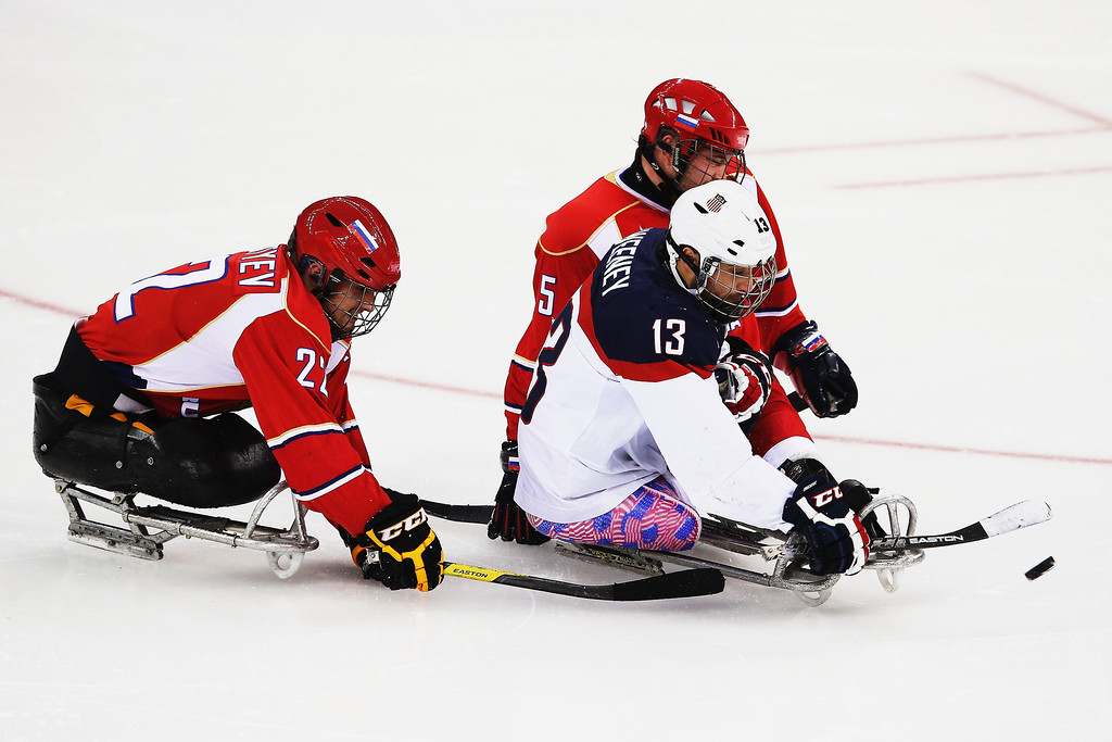 . Joshua Sweeney of the USA gets through Aleksei Lysov of Russia and Vasilii Varlakov of Russia during the ice sledge hockey gold medal game between the Russian Federation and the United States of America at the Shayba Arena during day eight of the 2014 Paralympic Winter Games on March 15, 2014 in Sochi, Russia.  (Photo by Hannah Peters/Getty Images)