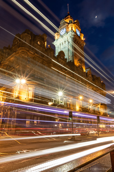 Edinburgh, Scotland - a long exposure captures double-decker bus lights zooming thru the city.