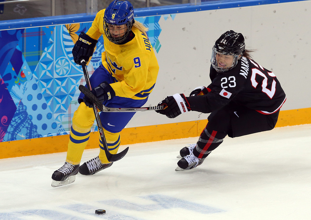. Ami Nakamura (R) of Japan fights for the pack with Josefine Holmgren (L) of Sweden during the match between Sweden and Japan at the Shayba Arena in the Ice Hockey tournament at the Sochi 2014 Olympic Games, Sochi, Russia, 09 February 2014  EPA/SRDJAN SUKI