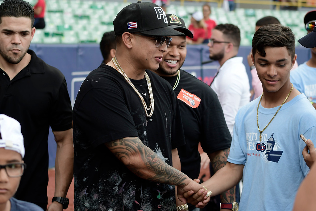 . Puerto Rican rapper Daddy Yankee greets youths on the field before the final game of a two-game Mayor League Series between the Minnesota Twins and the Cleveland Indians at the Hiram Bithorn Stadium in San Juan, Puerto Rico, Wednesday, April 18, 2018. (AP Photo/Carlos Giusti)