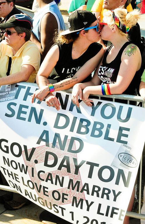 """. Mallory Strickling, right, and Jasmine Belille, both 27 from Eagan, kiss as they listen to speeches after Gov. Mark Dayton signed the same-sex marriage bill. \""""It\'s still surreal,\"""" said Belille, who said the couple is planning their wedding for Aug. 1. (Pioneer Press: Ben Garvin)"""