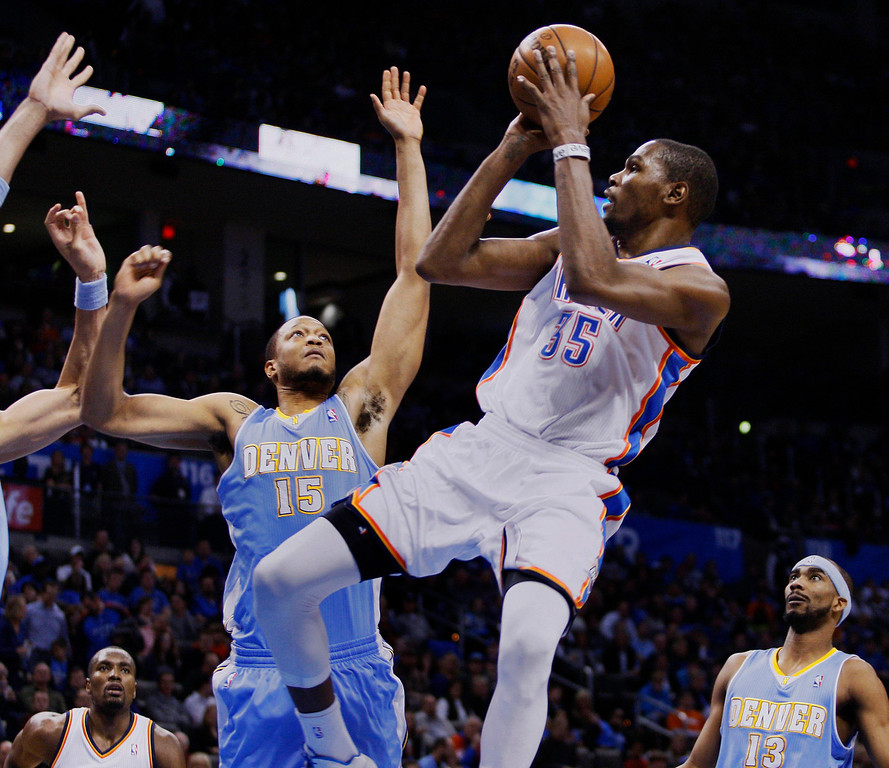 . Oklahoma City Thunder guard Kevin Durant (C) shoots against Denver Nuggets defenders Anthony Randolph (L) and Corey Brewer in the second half of their NBA basketball game in Oklahoma City, Oklahoma January 16, 2013. REUTERS/Bill Waugh