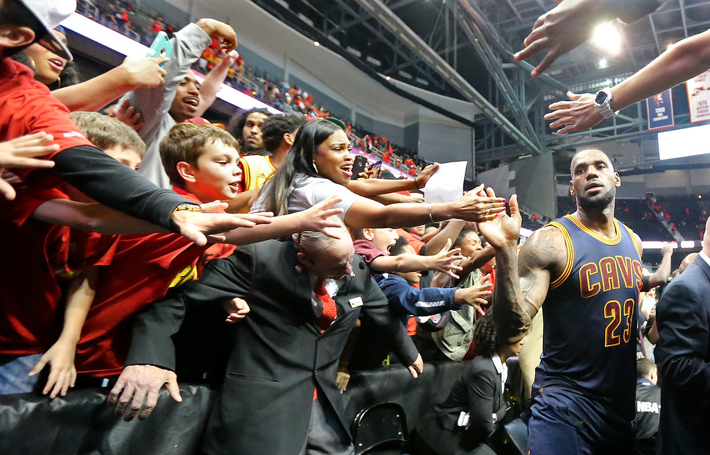 . Hawks fans reach for the Cleveland Cavaliers LeBron James as he leaves the court after the Cavaliers victory over the Hawks in Game 3 of a second-round NBA basketball playoff series Friday, May 6, 2016, in Atlanta. (Curtis Compton/Atlanta Journal-Constitution via AP)