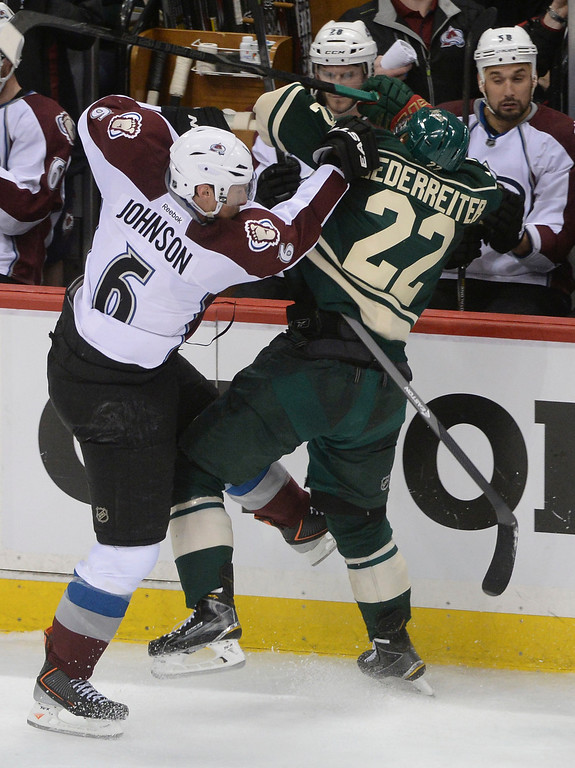 . Colorado defenseman Erik Johnson (6) checked Minnesota wing Nino Niederreiter (22) into the boards in the third period. The Minnesota Wild hosted the Colorado Avalanche at the Xcel Energy Center in St. Paul Monday night, April 21, 2014. (Photo by Karl Gehring/The Denver Post)