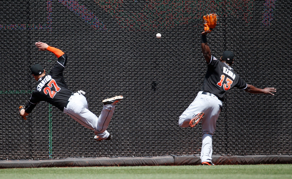 . Miami Marlins right fielder Giancarlo Stanton (27) and center fielder Marcell Ozuna (13) fall after colliding as the ball bounces away for an inside the park home run for Washington Nationals\' Ryan Zimmerman during the fourth inning of a baseball game at Nationals Park, Sunday, May 15, 2016, in Washington. Both players fell to the ground and stayed there until other players arrived to check on them, and they remained in the game. (AP Photo/Alex Brandon)