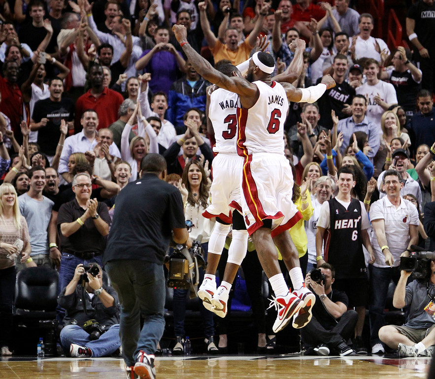 . Miami Heat\'s Dwyane Wade (3) and LeBron James (6) celebrate after Wade hit the game-winning shot during overtime of an NBA basketball game against the Indiana Pacers in Miami, Saturday, March 10, 2012. The Heat won 93-91. (AP Photo/J Pat Carter)