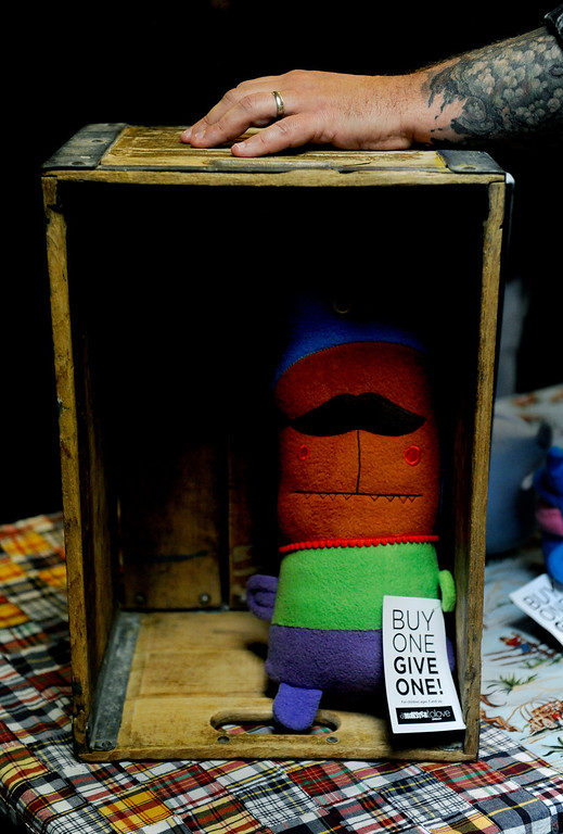 """. Ray Tollison rests his hand on a case that houses one of his monsters on Dec. 6 at the Holiday Mancraft 2013 craft fair at the VFW Post in Denver, Colo. \""""A Monster to Love\"""" was created by Tollison and his 12-year-old twin boys, who help design and sew the monsters. Photo by Jamie Cotten, Special to The Denver Post"""