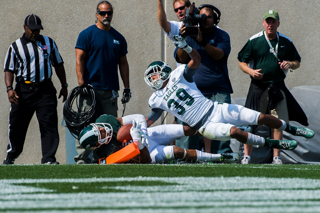 . Eastern Michigan freshman defensive back Jason Beck tackles Michigan State junior wide receiver AJ Troup into the end zone for a touchdown during the second quarter on Saturday, Sept. 20, 2014 at Spartan Stadium in East Lansing, Mich. (AP Photo/The Flint Journal, Jake May)