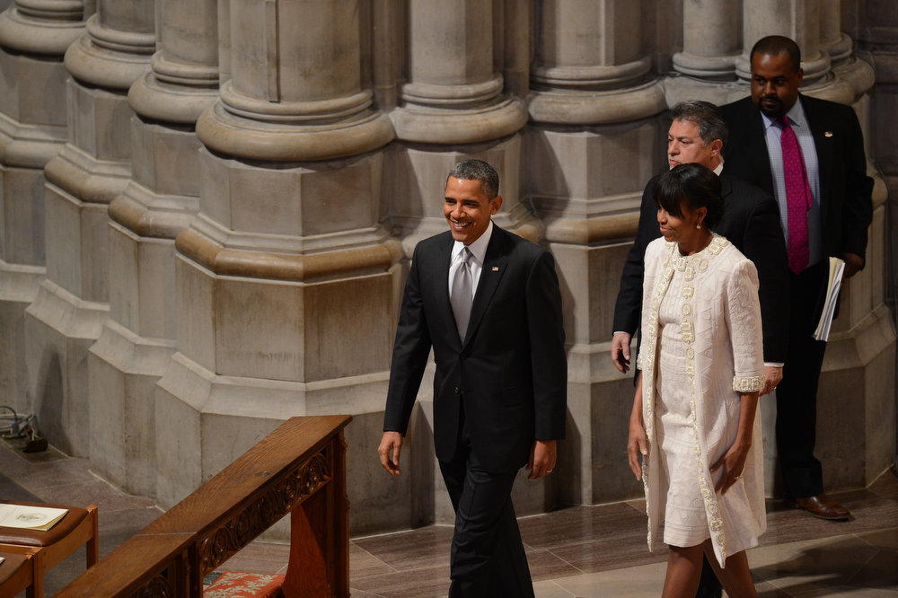 Description of . US President Barack Obama(L) and First Lady Michelle Obama arrive to attend a prayer service at Washington National Cathedral on January 22, 2013 in Washington, DC.  SAUL LOEB/AFP/Getty Images