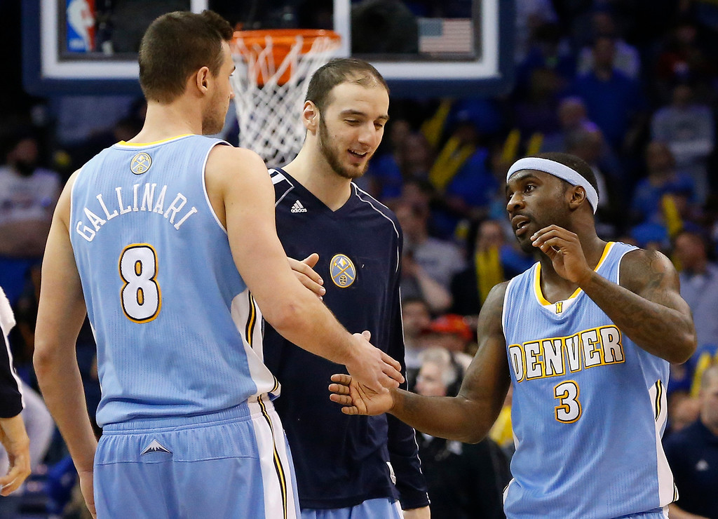 . Denver Nuggets guard Ty Lawson (3) is greeted by teammate Danilo Gallinari (8) as he walks off the court during a time out in the fourth quarter of an NBA basketball game against the Oklahoma City Thunder in Oklahoma City, Tuesday, March 19, 2013. Denver won 114-104. (AP Photo/Sue Ogrocki)