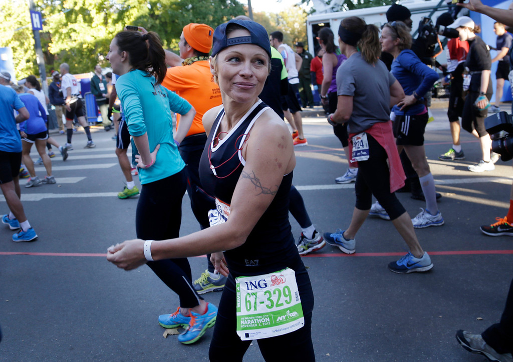 . Actress Pamela Anderson smiles after crossing the finish line at the 2013 New York City Marathon in New York, Sunday, Nov. 3, 2013.  (AP Photo/Seth Wenig)