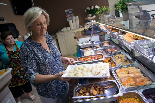 10/08/19 Wesley Bunnell | StaffrrElzbieta Kujawa , co owner of Euro Plate Restaurant located on Broad St, holds a tray of pierogi along with other prepared foods at her restaurant which serves ready to go meals on Tuesday October 8, 2019. Tuesday was national pierogi day.