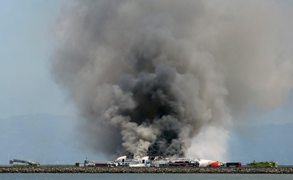 . Smokes rises from Asiana Flight 214 after it crashed at San Francisco International Airport in San Francisco, Saturday, July 6, 2013. (AP Photo/Bay Area News Group, John Green)