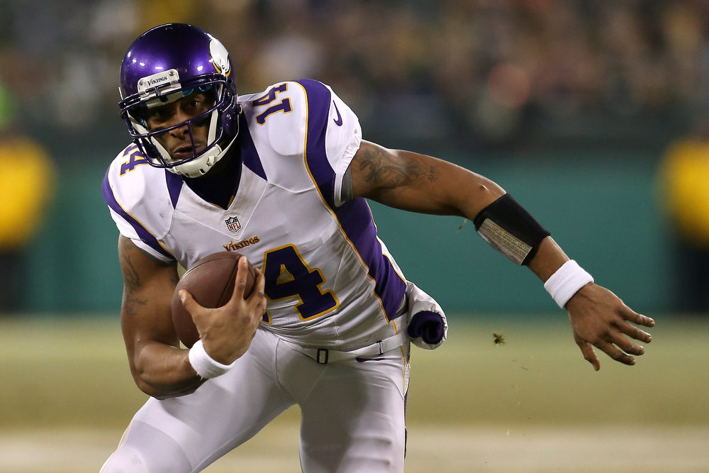 . Quarterback Joe Webb #14 of the Minnesota Vikings runs the ball against the Green Bay Packers in the first quarter during the NFC Wild Card Playoff game at Lambeau Field on January 5, 2013 in Green Bay, Wisconsin.  (Photo by Jonathan Daniel/Getty Images)