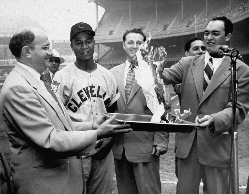 """. Larry Doby of the Cleveland Indians smiles as radio announcer Mel Allen (right) gives the slow burn to the $3,500 mortgage on Larry\'s home in Paterson, N.J., during \""""Larry Doby Day\"""" ceremonies at Yankee Stadium in New York, June 23, 1951, before the start of the Yankees - Indians game.  The mortgage was paid off by people of Paterson.  At left is Joe Gooter, sports editor of the Paterson Evening News, and second from right is Paterson\'s Mayor Mike DeVita. (AP Photo/stf)"""