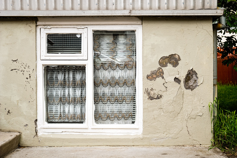 I was drawn to the similarity of the window curtain pattern and colors to the chipped wall stucco.