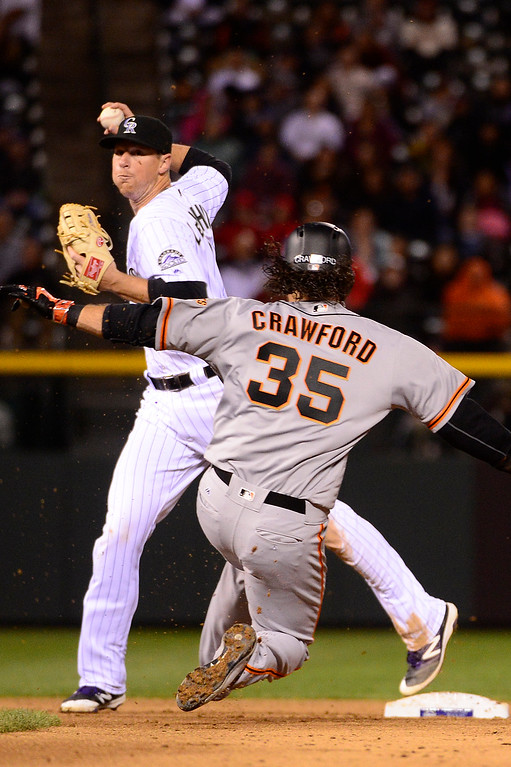 . DENVER, CO - APRIL 12: Colorado Rockies second baseman DJ LeMahieu (9) makes a throw to first after tagging out San Francisco Giants shortstop Brandon Crawford (35) during the sixth inning at Coors Field on April 12, 2016 in Denver, Colorado. San Francisco Giants defeated the Colorado Rockies 7-2. (Photo by Brent Lewis/The Denver Post)