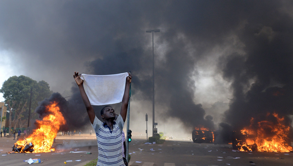 . A protester holds a white cloth as cars and documents burn outside the parliament in Ouagadougou on October 30, 2014. Hundreds of angry demonstrators in Burkina Faso stormed parliament on October 30 before setting it on fire in protest at plans to change the constitution to allow President Blaise Compaore to extend his 27-year rule. ISSOUF SANOGO/AFP/Getty Images