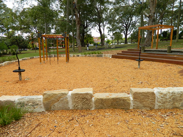 sandstone block retaining wall and spinners and timber seating steps and open cubby and climbing frame with cargo net