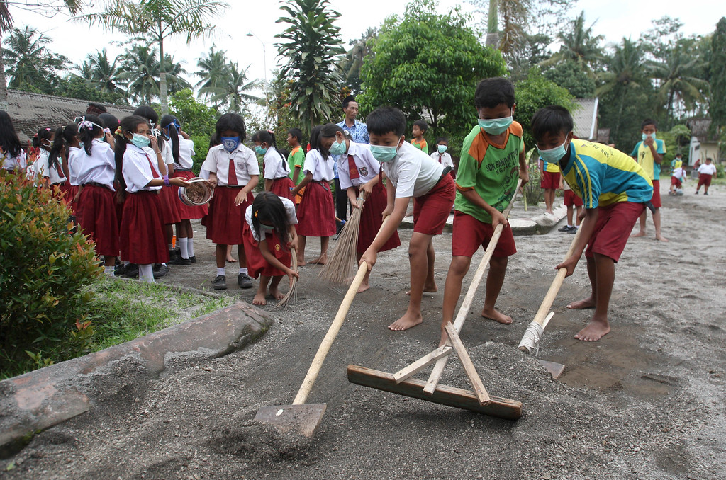 . Students clean the school yard which was covered with volcanic ash following an eruption of Mount Kelud in Kediri, East Java, Indonesia, Monday, Feb. 17, 2014. (AP Photo/Trisnadi)