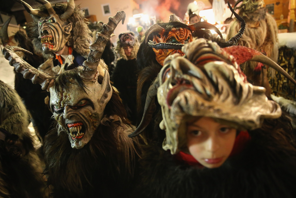 . Young children dressed as the Krampus creature wait to parade during Krampus night on November 30, 2013 in Neustift im Stubaital, Austria. Sixteen Krampus groups including over 200 Krampuses participated in the first annual Neustift event. Krampus, in Tyrol also called Tuifl, is a demon-like creature represented by a fearsome, hand-carved wooden mask with animal horns, a suit made from sheep or goat skin and large cow bells attached to the waist that the wearer rings by running or shaking his hips up and down. Krampus has been a part of Central European, alpine folklore going back at least a millennium, and since the 17th-century Krampus traditionally accompanies St. Nicholas and angels on the evening of December 5 to visit households to reward children that have been good while reprimanding those who have not. However, in the last few decades Tyrol in particular has seen the founding of numerous village Krampus associations with up to 100 members each and who parade without St. Nicholas at Krampus events throughout November and early December.  (Photo by Sean Gallup/Getty Images)