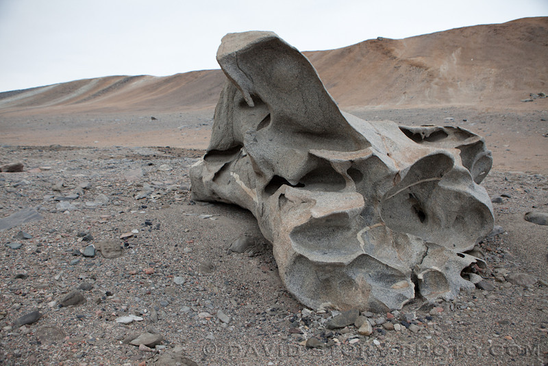 Ventifact: a rock sculpted by aeolian transport.