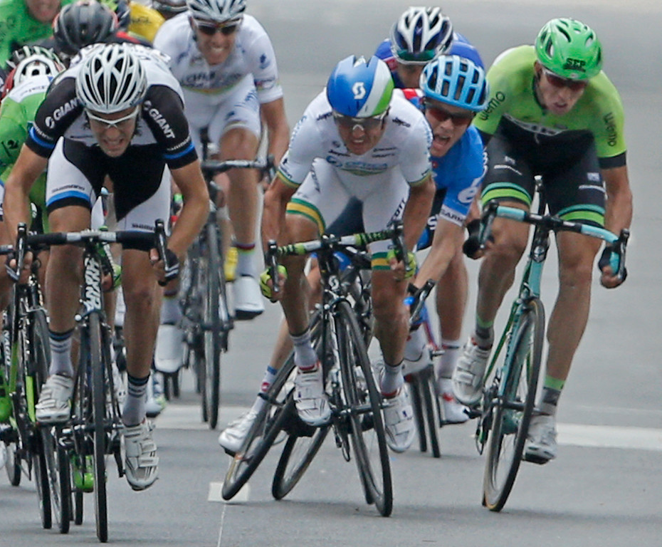 . Andrew Talansky of the U.S., in blue, looses his balance as he touches the rear wheel of Australia\'s Simon Gerrans, center in white, during the sprint of the pack in the seventh stage of the Tour de France cycling race over 234.5 kilometers (145.7 miles) with start in Epernay and finish in Nancy, France, Friday, July 11, 2014. Talansky crashed but finished the race. (AP Photo/Peter Dejong)
