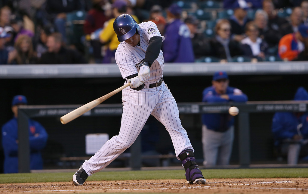 . Nolan Arenado #28 of the Colorado Rockies hits a single off of starting pitcher Bartolo Colon #40 of the New York Mets in the third inning at Coors Field on May 1, 2014 in Denver, Colorado. Arenado extended his league leading consecutive game hit streak to 21 games.  (Photo by Doug Pensinger/Getty Images)