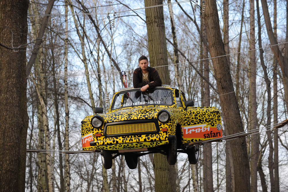 ". Maik Dannewitzsch poses in a Trabant car (""Trabi\"") he fixed on March 20, 2012 in the high ropes course of the adventure park Moritzburg near Dresden, eastern Germany.  The vintage car from the former German Democratic Republic (GDR) will be a new attraction when the park opens its doors for the season on March 31, 2012.         AFP PHOTO / MATTHIAS HIEKEL"