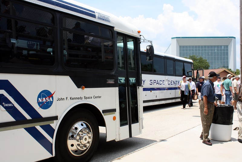 Buses drop off VIP guests at the Banana Creek viewing area, with the Apollo / Saturn V Center in the background.