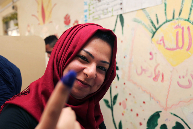 Description of . An Iraqi woman shows her ink-stained finger after casting her vote inside a polling station for parliamentary elections in Baghdad, Iraq, Wednesday, April 30, 2014. Iraq is holding its third parliamentary elections since the U.S.-led invasion that toppled dictator Saddam Hussein.  More than 22 million voters are eligible to cast their ballots to choose 328 lawmakers out of more than 9,000 candidates. (AP Photo/Karim Kadim)