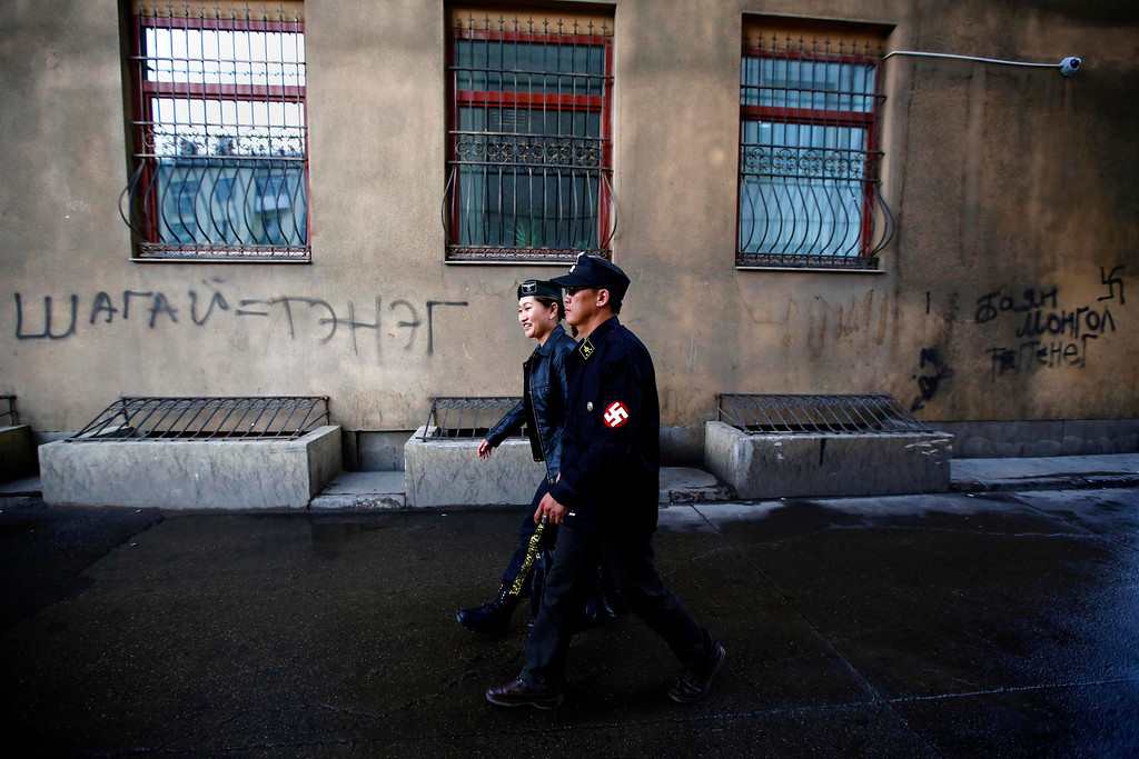 . Ariunbold and Uranjargal (L), leaders of the Mongolian neo-Nazi group Tsagaan Khass, leave the group\'s headquarters in Ulan Bator June 22, 2013. The group has rebranded itself as an environmentalist organisation fighting pollution by foreign-owned mines, seeking legitimacy as it sends Swastika-wearing members to check mining permits. Over the past years, ultra-nationalist groups have expanded in the country and among those garnering attention is Tsagaan Khass, which has recently shifted its focus from activities such as attacks on women it accuses of consorting with foreign men to environmental issues, with the stated goal of protecting Mongolia from foreign mining interests. This ultra-nationalist group was founded in the 1990s and currently has 100-plus members. Picture taken June 22, 2013. REUTERS/Carlos Barria