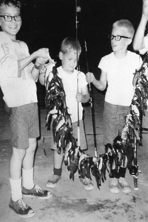 ". We recycled the envelope in which this picture came, before we realized that the contributor had failed to note his (or, of course, her) identity on either the picture or the sheet of paper that included this caption: ""Summer Fishing: Mike, Jeff and Jon Seeman caught these 75 bullheads and carp in Moore Lake in Fridley in the mid-\'60s.\"""