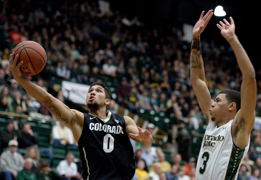. University of Colorado\'s Askia Booker drives to the hoop in front of Marcus Holt during an NCAA game against Colorado State University on Tuesday, Dec. 3, 2013, at the Moby Arena in Fort Collins. Jeremy Papasso/ Camera