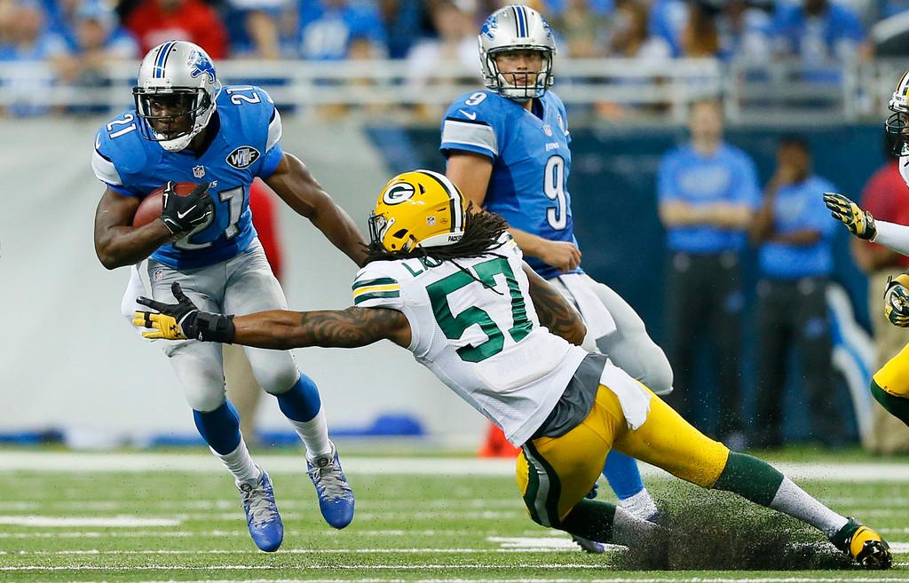 . Green Bay Packers inside linebacker Jamari Lattimore (57) reaches in on Detroit Lions running back Reggie Bush (21) during the second half of an NFL football game in Detroit, Sunday, Sept. 21, 2014. (AP Photo/Rick Osentoski)