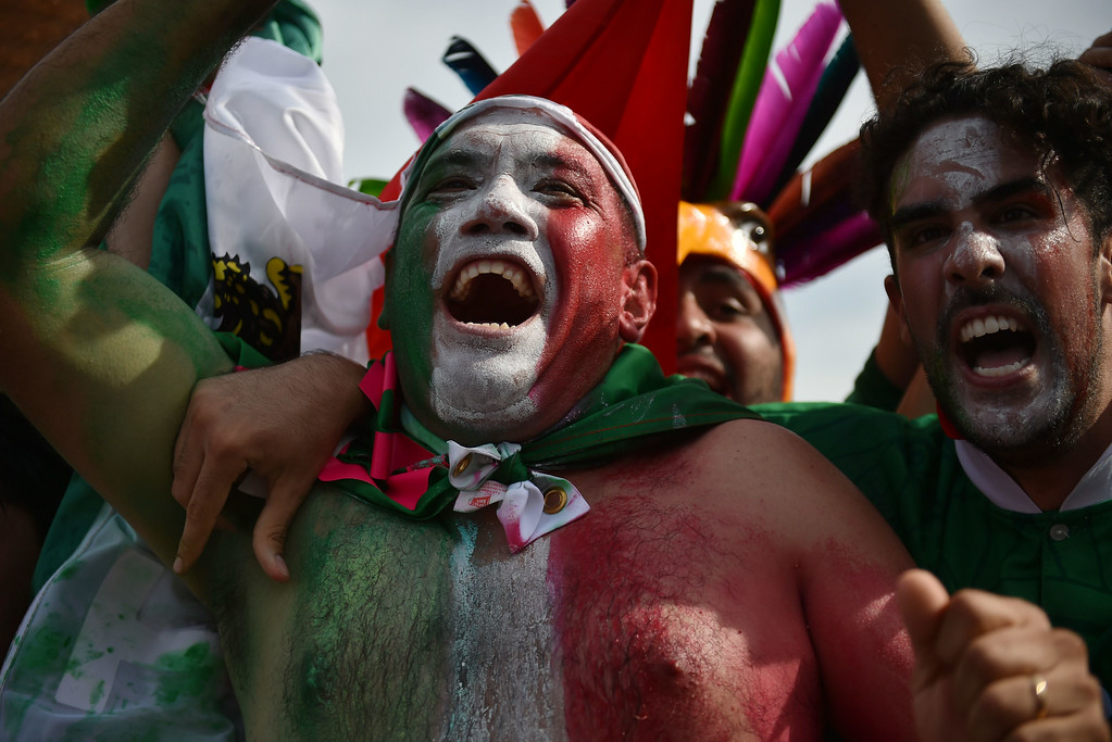 . Mexico\'s fans celebrate after Mexico scored a goal during their Round of 16 football match against the Netherlands as they watch the game at Fanfesta\'s live projection at Copacabana beach in Rio de Janeiro on June 29, 2014 during the 2014 FIFA World Cup tournament. AFP PHOTO / YASUYOSHI CHIBA