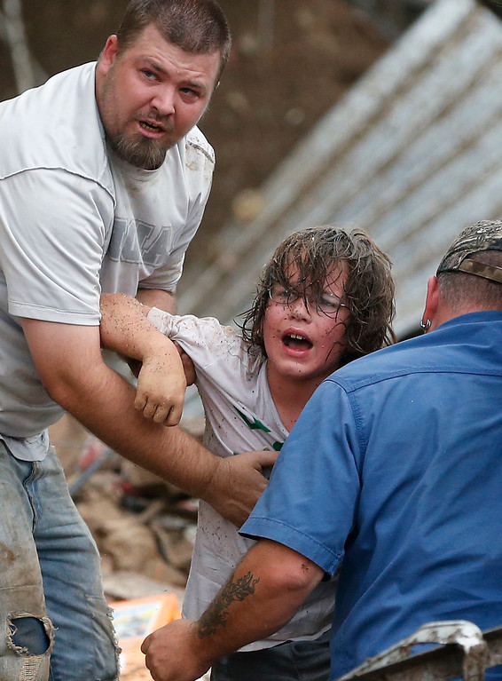 . In this May 20, 2013, file photo, a child calls to his father after being pulled from the rubble of the Tower Plaza Elementary School following a tornado in Moore, Okla. (AP Photo Sue Ogrocki, File)