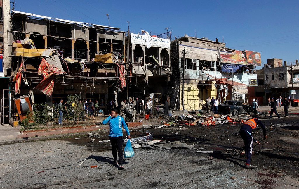 . Residents gather at the site of a car bomb attack in the AL-Mashtal district in Baghdad March 19, 2013.  REUTERS/Mohammed Ameen