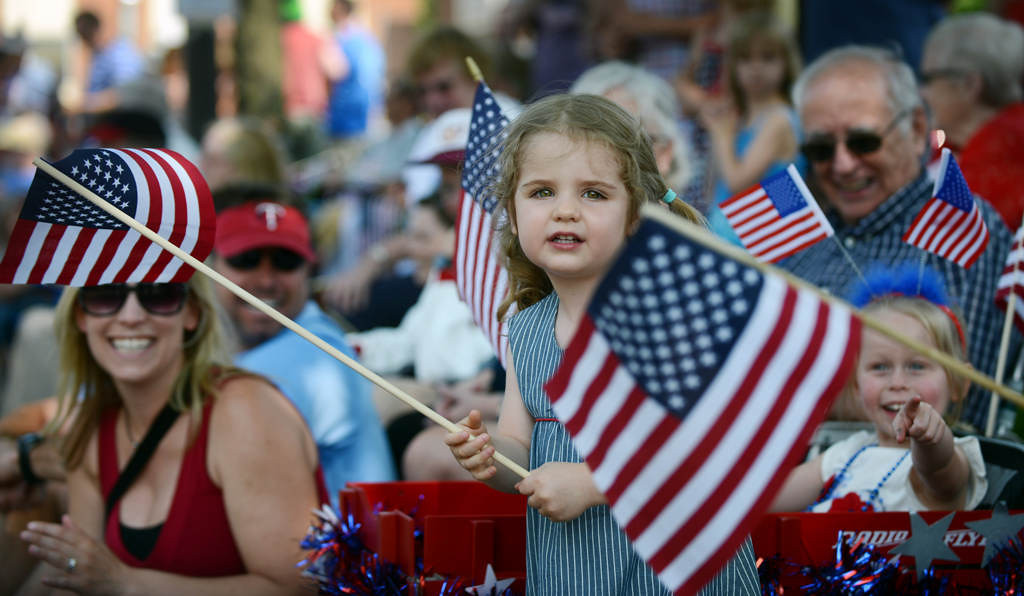 . Willa Brubaker, 3, of Minneapolis waves a flag as she watches the annual Fourth of July parade make its way along Como Avenue in St. Paul\'s St. Anthony Park neighborhood on Thursday, July 4, 2013. It\'s St. Paul\'s only Independence Day parade, followed by an an all-day, family-friendly picnic and party in nearby Langford Park. (Pioneer Press: Chris Polydoroff)