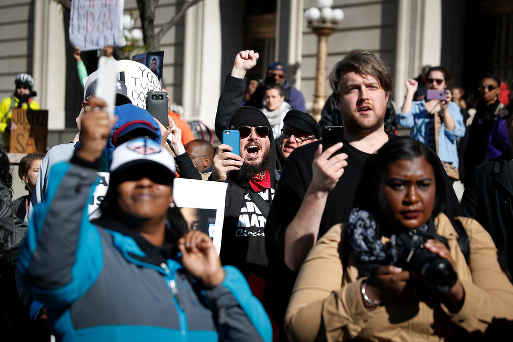 . Protestors chant outside the Hamilton County Courthouse after a mistrial is declared due to a hung jury in the murder trial against Ray Tensing, Saturday, Nov. 12, 2016, in Cincinnati. Tensing, the former University of Cincinnati police officer, is charged with murdering Sam DuBose while on duty during a routine traffic stop on July 19, 2015. (AP Photo/John Minchillo)